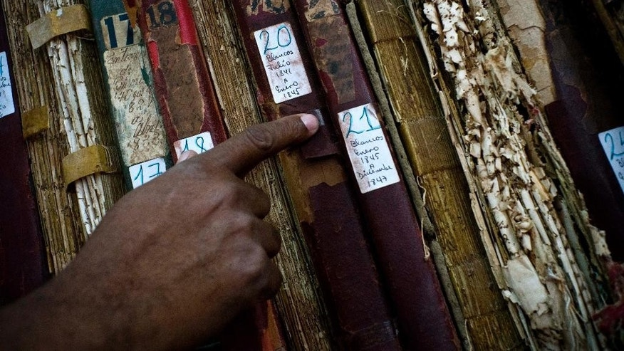 "This Jan. 12, 2017 photo shows a man searching among volumes labeled ""Whites"" as part of an effort to digitize colonial-era registries of blacks and whites at the Espiritu Santo Church in Old Havana, Cuba. ""That's how these books where placed, books for whites, books for blacks. The important thing is to preserve as many of them as possible,"" said church Deacon Felix Knights. (AP Photo/Ramon Espinosa)"