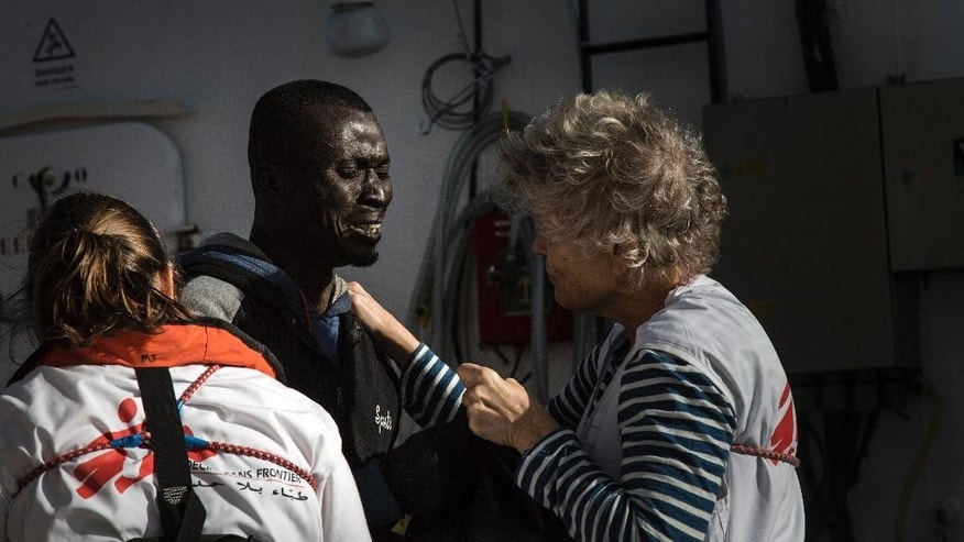 A migrant reacts as he is greeted by MSF workers aboard the MV Aquarius, as 193 people and two corpses are recovered Friday Jan. 13, 2017, from international waters in the Mediterranean Sea about 22 miles (35 Km) north of Sabrata, Libya.  The MV Aquarius search and rescue vessel operated by MSF and SOS Mediterranee picked up 183 male and 10 female migrants, thought to have originated from African countries including Nigeria, Gambia and Senegal. The migrants are expected to disembark in Italy. (AP Photo/Sima Diab)