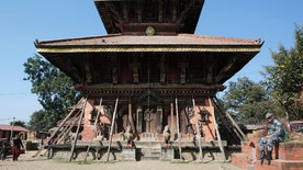 In this Nov. 22, 2016 photo, a Nepalese policeman rests in front of Changu Narayan, a temple dedicated to Lord Vishnu, at Changu Village, 20 kilometers (12.5 miles) east of Kathmandu, Nepal. Less than two years after a 7.8 magnitude earthquake damaged the 5th century temple, the community is cleaning up their World Heritage site themselves and British architect John Sanday, who led the World Monuments Fund restoration of Cambodia's Angkor Wat, has taken on the recovery as his pet project. Changu Narayan is believed to be the oldest Hindu place of worship in the country, its wooden walls intricately carved with hundreds of deities, perched atop a steep hill overlooking the Kathmandu Valley. (AP Photo/Niranjan Shrestha)