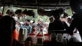 FILE - In this Dec. 2, 2016 file photo, Rohingya from Myanmar watch a television program about them being shown on a mobile phone inside a tea stall at an unregistered refugee camp in Teknaf, near Cox's Bazar, a southern coastal district about, 296 kilometers (183 miles) south of Dhaka, Bangladesh. Muslim villagers in western Myanmar's troubled Rakhine state said Sunday, Jan. 15, 2017, that they hope positive change will result from a U.N. envoy's visit to the region, where soldiers are accused of widespread abuses against minority Muslims, including murder, rape and the burning of thousands of homes. (AP Photo/A.M. Ahad, File)