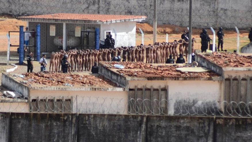 Naked inmates stand in line while surrounded by police after a riot at the Alcacuz prison in Nisia Floresta, Rio Grande do Norte state, Brazil, Sunday, Jan. 15, 2017. Security authorities said Sunday they have regained control of two Brazilian prisons after several inmates were killed during a riot,  the latest in a string of prison disturbances across the country. (Frankie Marcone/Futura Press via AP) NAO PUBLICAR NO BRASIL