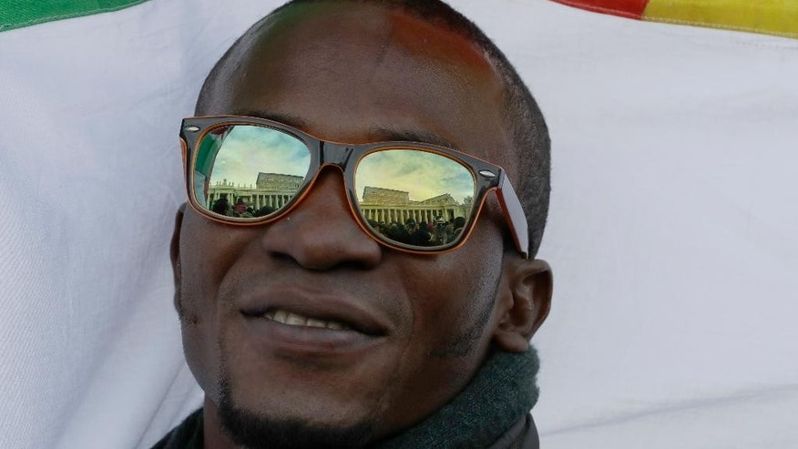 The Apostolic palace is reflected on the glasses of a migrant attending the Angelus noon prayer delivered by Pope Francis in St. Peter's Square at the Vatican, Sunday, Jan.15, 2017. (AP Photo/Andrew Medichini)