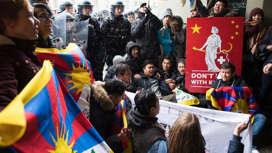 People protest in front of the police for a free Tibet and against the visit of China's President Xi Jinping  in Bern, on Sunday, Jan. 15, 2017. (Anthony Anex/Keystone via AP)