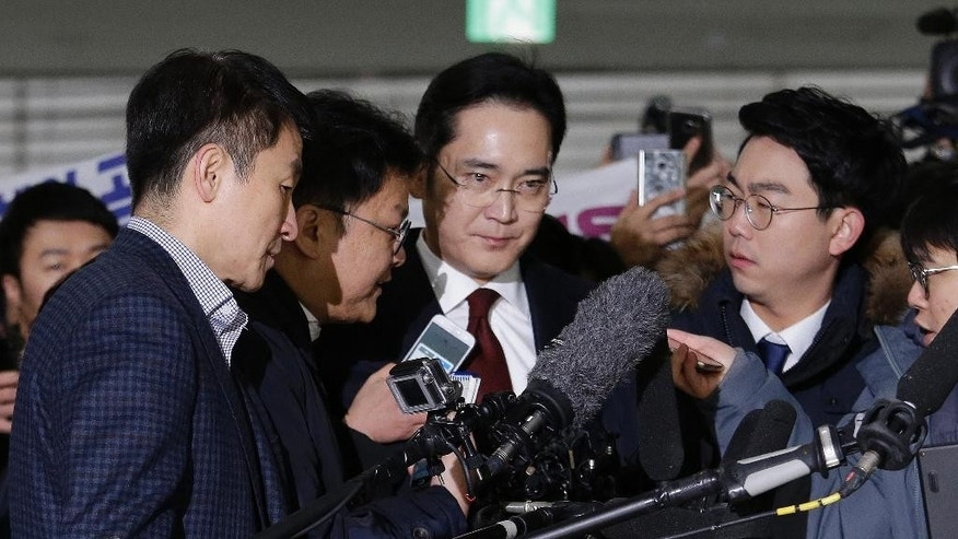 FILE - In this  Jan. 12, 2017 fie photo, Lee Jae-yong, center, vice chairman of Samsung Electronics, arrives to be questioned as a suspect in bribery case in the massive influence-peddling scandal that led to the president's impeachment at the office of the independent counsel in Seoul, South Korea. The special prosecutors office said Monday, Jan. 16, 2017 that it requested an arrest warrant for Lee, the 48-year-old Samsung Electronics vice chairman. (AP Photo/Ahn Young-joon, Pool, File)