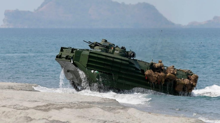 FILE - In this April 21, 2015 file photo, a U.S. Navy's amphibious assault vehicle with Philippine and U.S. troops on board storms the beach at a combined assault exercise at a beach facing one of the contested islands in the South China Sea known as the Scarborough Shoal in the West Philippine Sea at the Naval Education and Training Command at San Antonio township, Zambales province, northwest of Manila, Philippines. China is watching carefully whether the incoming U.S. administration will raise tensions in the region after Donald Trump's choice for secretary of state said last week the U.S. should deny Beijing access to its man-made islands. (AP Photo/Bullit Marquez, File)