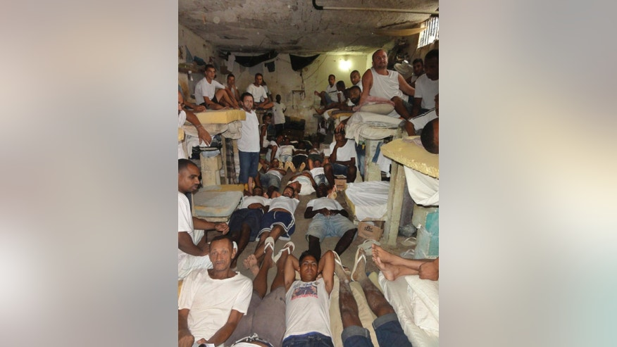 FILE - This Jan. 18, 2016 file photo attained by the Associated Press shows prisoners in a crowded cell, some on the floor, at the Instituto Penal Placido de Sa Carvalho in Rio de Janeiro, Brazil. Brazilian authorities are scrambling to find ways to stop a wave of prison violence that has killed at least 125 inmates in early Jan. 2017, many decapitated and with their hearts and intestines ripped out. (AP Photo, File)