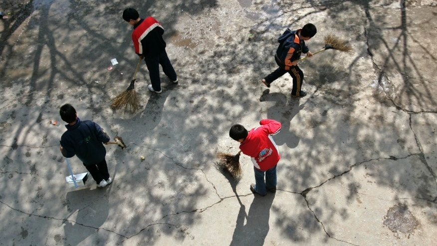Children sweep the playground at a rural primary school in Nanhui district on the outskirts of Shanghai.
