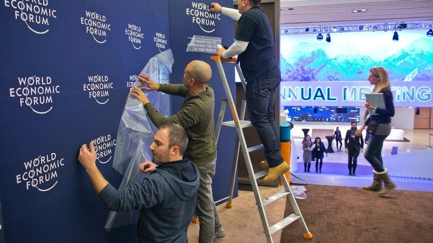 Staff members put up logos of the World Economic Forum at the Congress Center in Davos, Switzerland, Monday, Jan. 16, 2017. Business and world leaders are gathering for the annual meeting World Economic Forum in Davos. (AP Photo/Michel Euler)
