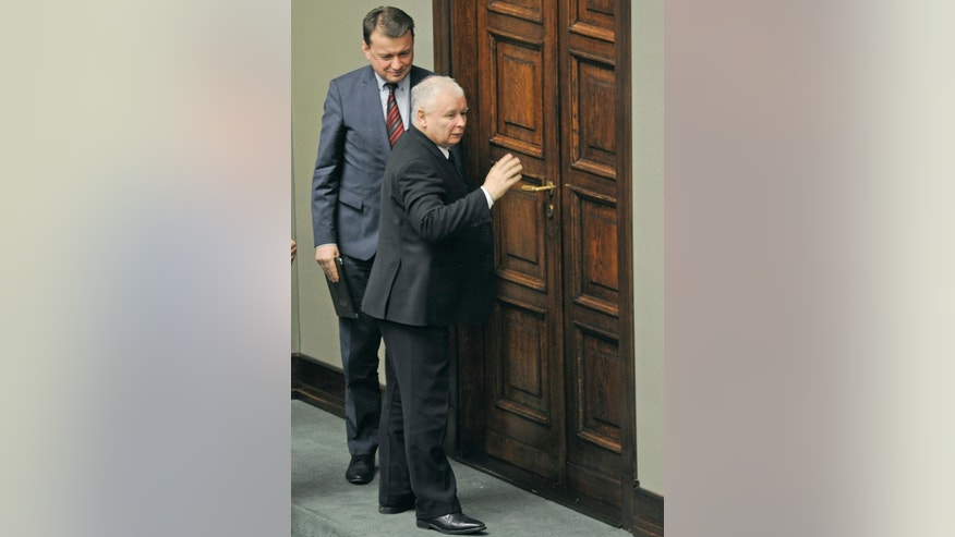 Jaroslaw Kaczynski, right, the leader of the ruling Law and Justice party walks out of the session hall as Interior Minister Mariusz Blaszczak stands behind, after the speaker opened the parliament session, only to declare a break till Thursday, in Warsaw, Poland, Wednesday, Jan. 11, 2017. The parliament's session hall is occupied by a group of opposition lawmakers as they continue a protest since Dec.16, 2016 against the policies of the ruling Law and Justice party, causing delay to the first session of 2017. (AP Photo/Alik Keplicz)