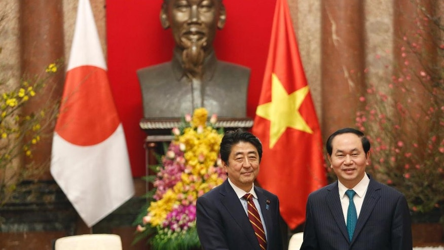 Vietnam's President Tran Dai Quang, right, and Japanese Prime Minister Shinzo Abe shake hands at the Presidential Palace in Hanoi, Vietnam, Monday, Jan. 16, 2017. Abe is on a two-day official visit to Vietnam. (Kham/Pool Photo via AP)