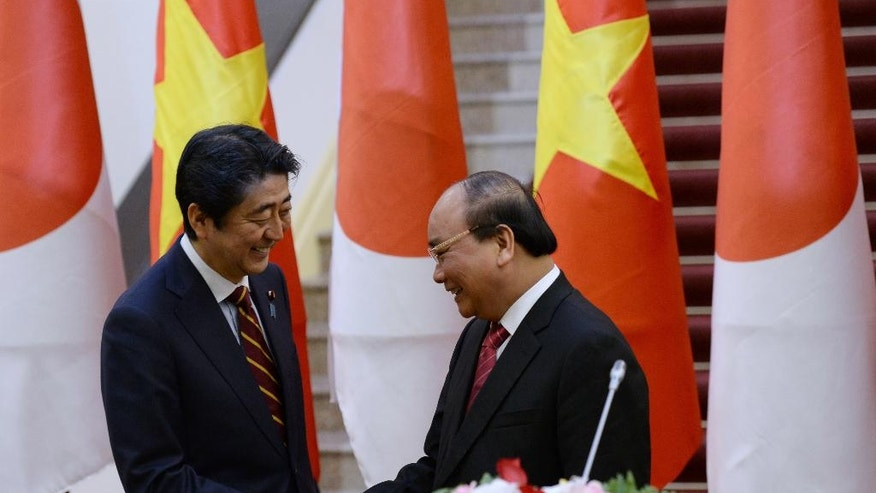 Vietnamese Prime Minister Nguyen Xuan Phuc, right, and Japanese Prime Minister Shinzo Abe shake hands at the end of a joint press briefing following their meeting at Phuc's Cabinet Office in Hanoi, Vietnam, Monday, Jan. 16, 2017. Abe is on a two-day official visit to Vietnam. (Hoang Dinh Nam/Pool Photo via AP)
