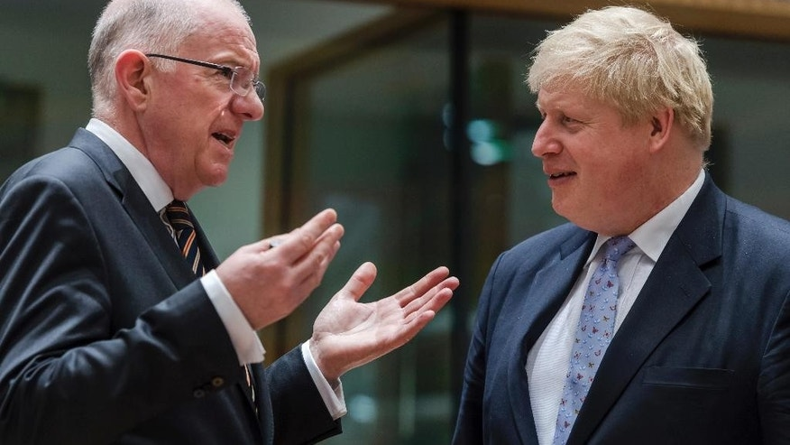 British Foreign Secretary Boris Johnson, right, talks with Ireland's Foreign Minister Charles Flanagan during an EU foreign ministers meeting at the EU Council in Brussels on Monday, Jan. 16, 2017. (AP Photo/Geert Vanden Wijngaert)