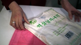 In this Jan. 9, 2017, photo, a saleswoman shows off a locally produced t-shirt and towel made out of Hemp in Pyongyang, North Korea, which has been getting some pretty high praise lately from the stoner world. The claim that marijuana is legal in North Korea and that if any laws do exist they aren't enforced is emphatically not true according to the North Korean penal code, which lists it as a controlled substance in the same category as cocaine and heroin, and the people who would likely be called in to try to get any foreigner violating them out of jail. Hemp is, in fact, grown in North Korea with official sanction. It's used to make cooking oil and military uniforms and belts. (AP Photo/Wong Maye-E)