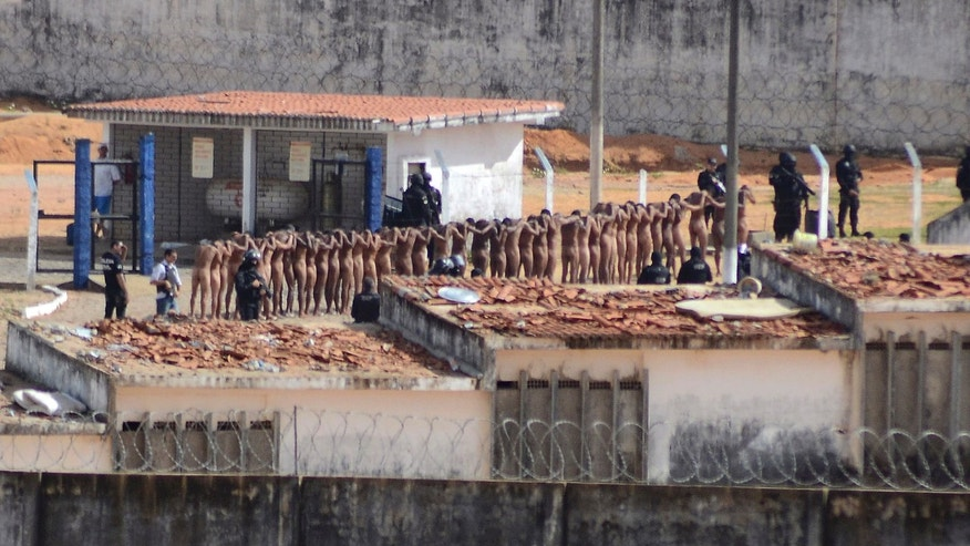 Naked inmates stand in line while surrounded by police after a riot at the Alcacuz prison in Nisia Floresta, Rio Grande do Norte state, Brazil, Sunday, Jan. 15, 2017.