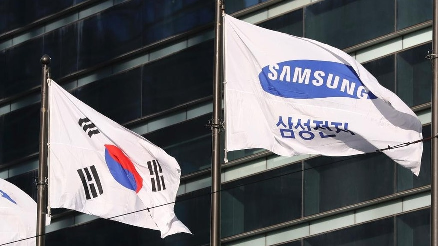 The company flag of Samsung Electronics flutters next to the South Korean national flag in Seoul, South Korea, Monday, Jan. 16, 2017. Prosecutors requested the arrest Monday of the de facto head of Samsung, South Korea's biggest company, on bribery and other charges in the influence-peddling scandal that led to the impeachment of the country's president. (AP Photo/Lee Jin-man)