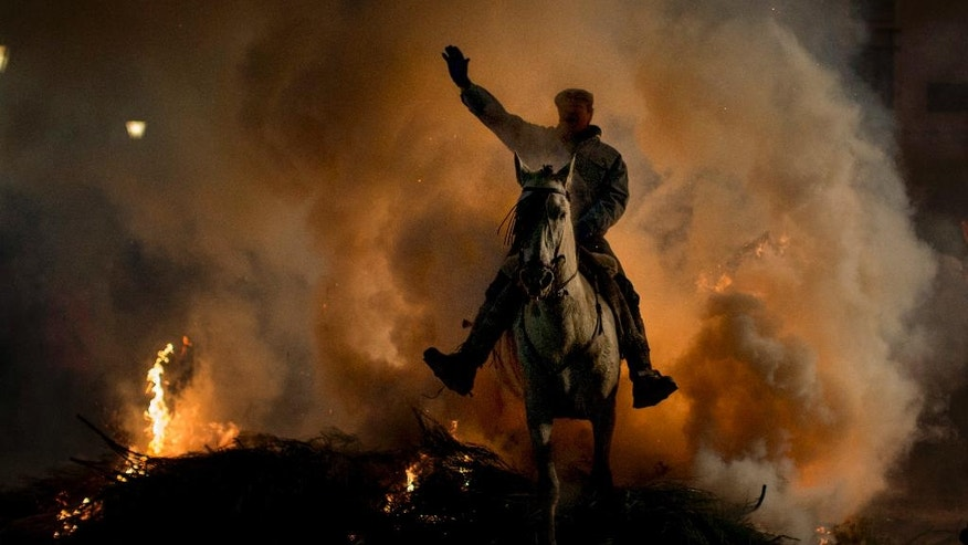 "A man rides a horse through a bonfire as part of a ritual in honour of Saint Anthony the Abbot, the patron saint of domestic animals, in San Bartolome de Pinares, about 100 km west of Madrid, Spain, on Monday, Jan. 16, 2017. On the eve of Saint Anthony's Day, hundreds ride their horses through the narrow cobblestone streets of the small village of San Bartolome during the ""Luminarias,"" a tradition that dates back 500 years and is meant to purify the animals with the smoke of the bonfires and protect them for the year to come. (AP Photo/Emilio Morenatti)"