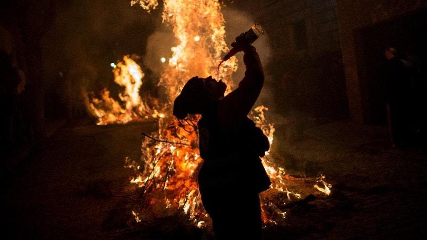 "A woman drinks wine man next to a bonfire as part of a ritual in honor of Saint Anthony the Abbot, the patron saint of domestic animals, in San Bartolome de Pinares, about 100 km west of Madrid, Spain on Monday, Jan. 16, 2017. On the eve of Saint Anthony's Day, hundreds ride their horses through the narrow cobblestone streets of the small village of San Bartolome during the ""Luminarias,"" a tradition that dates back 500 years and is meant to purify the animals with the smoke of the bonfires and protect them for the year to come. (AP Photo/Emilio Morenatti)"