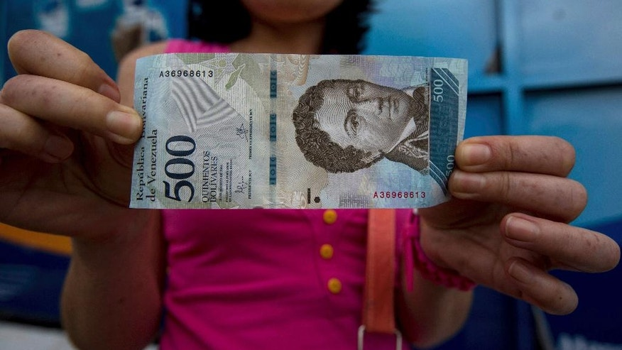 A bank customer shows a new bank note of 500 Bolivars outside a bank in Caracas, Venezuela, Monday, Jan. 16, 2017. As the nation experiences triple-digit inflation, the government rolled out larger denomination bank notes on Monday, ranging in value from 500 to 20,000 bolivars. (AP Photo/Fernando Llano)