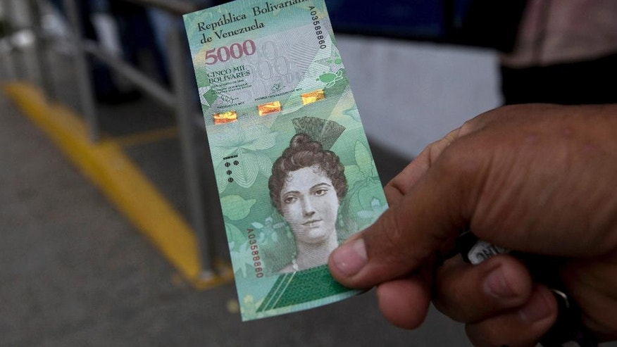 A man shows a new bank note of 5,000 Bolivars outside a bank in Caracas, Venezuela, Monday, Jan. 16, 2017.  As the nation experiences triple-digit inflation, the government rolled out larger denomination bank notes on Monday, ranging in value from 500 to 20,000 bolivars. (AP Photo/Fernando Llano)