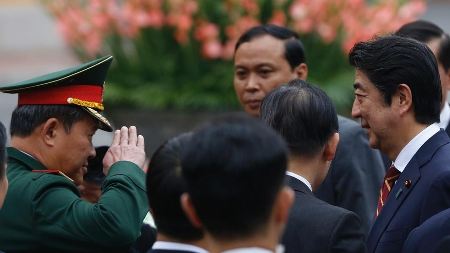 Vietnam's Vice Minister of Defence Be Xuan Truong, left, salutes Japan's Prime Minister Shinzo Abe, right, during a welcoming ceremony at the Presidential Palace in Hanoi, Monday, Jan. 16, 2017. Abe is on a two-day official visit to Vietnam. (Kham/Pool photo via AP)