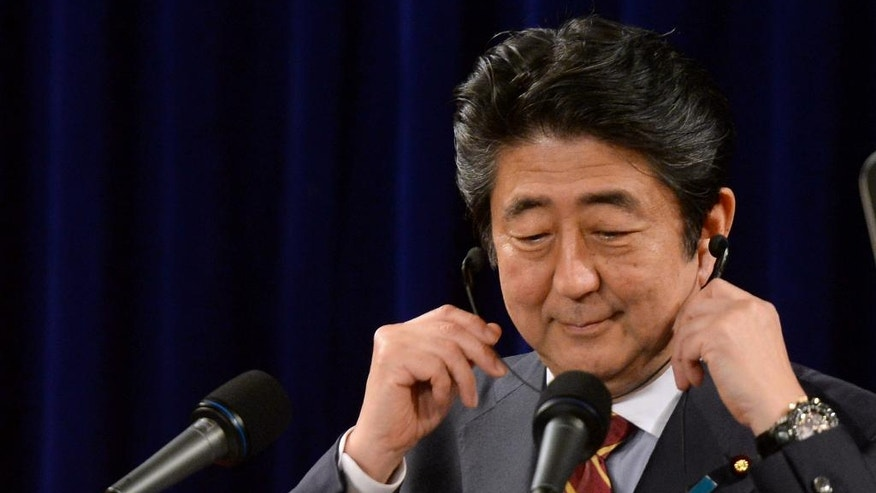 Japanese Prime Minister Shinzo Abe puts on earphones as he takes a question during a press conference in Hanoi, Vietnam, Monday, Jan. 16, 2017. Japan will provide Vietnam new patrol vessels, Abe said Monday on the last stop of his four-nation tour to boost his country's trade and security engagements in Asia amid China's rising dominance. (Hoang Dinh Nam/Pool Photo via AP)