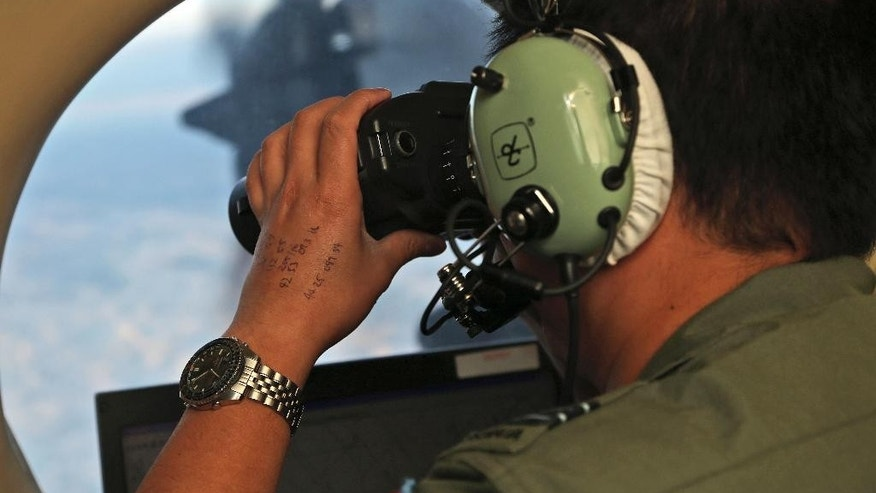 FILE - In this March 22, 2014, file photo, Flight Officer Jack Chen uses binoculars at an observers window on a Royal Australian Air Force P-3 Orion during the search for missing Malaysia Airlines Flight MH370 in Southern Indian Ocean, Australia. The Joint Agency Coordination Center in Australia said Tuesday, Jan. 17, 2017 that the search for Malaysia Airlines Flight 370 had officially been suspended after crews finished their fruitless sweep of the 120,000-square kilometer (46,000-square mile) search zone west of Australia. (AP Photo/Rob Griffith, File)