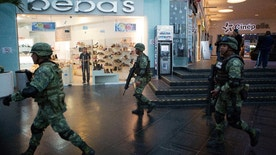 Soldiers walk inside Plaza Las Americas mall following reports of gunfire in Cancun, Mexico, Tuesday, Jan. 17, 2017. Gunmen attacked the state prosecutor's office in this Caribbean resort city Tuesday, ratcheting up tensions just a day after a deadly shooting at a music festival in a nearby town. (AP Photo/Rebecca Blackwell)