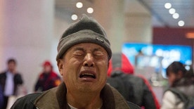 Wen Wanchang, whose son was on board the missing Malaysia Airlines Flight 370, reacts to journalists filming him as he arrives at the train station in Beijing, China, Tuesday, Jan. 17, 2017. Some relatives of Flight 370's passengers expressed anger, disappointment and a resolve to press authorities to resume their efforts and find out exactly what happened. Others said they understood that the search — the most expensive of its kind in aviation history — had to come to an end. (AP Photo/Ng Han Guan)