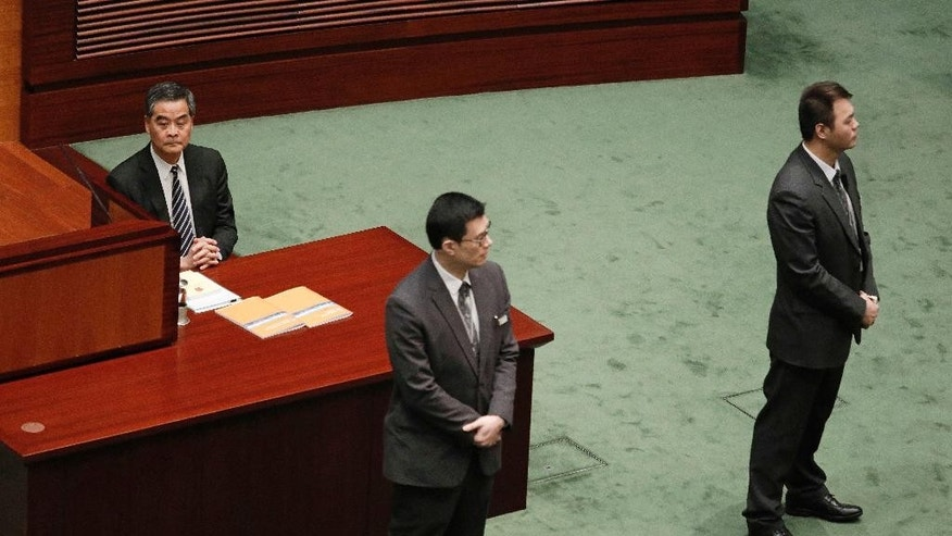 Security guardsvstand in front of Hong Kong's Chief Executive Leung Chun-ying, left, during a break in his final policy speech at Legislative Council in Hong Kong, Wednesday, Jan. 18, 2017. Hong Kong's outgoing leader has issued a warning in his farewell policy speech to those advocating independence for the Chinese-controlled territory. (AP Photo/Vincent Yu)