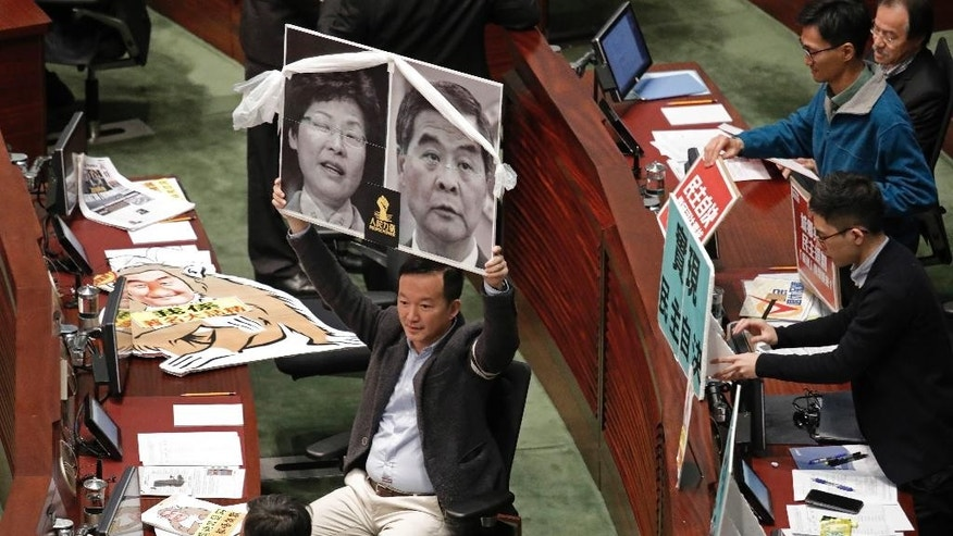 A lawmaker raises pictures of Hong Kong's Chief Executive Leung Chun-ying and former Chief Secretary Carrie Lam during Leung's final policy speech at the Legislative Council in Hong Kong, Wednesday, Jan. 18, 2017. Hong Kong's outgoing leader has issued a warning in his farewell policy speech to those advocating independence for the Chinese-controlled territory. (AP Photo/Vincent Yu)