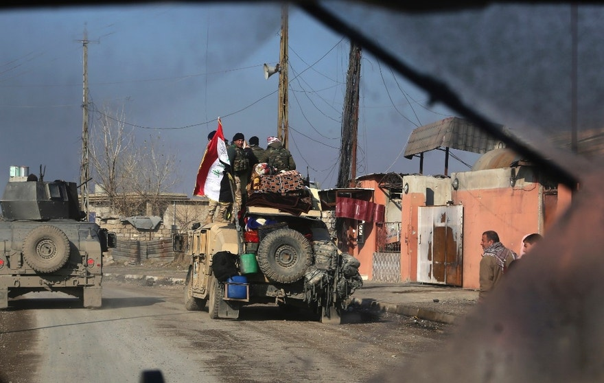 In this photo picture taken through the windshield of Iraq's special forces armored vehicle, Iraqi security forces advance in the eastern side of Mosul, Iraq, Monday, Jan. 16, 2017. Iraqi troops have begun to push Islamic State militants out of the last remaining neighborhoods between government-held territory in the eastern Mosul and the Tigris river which divides the city. (AP Photo/ Khalid Mohammed)