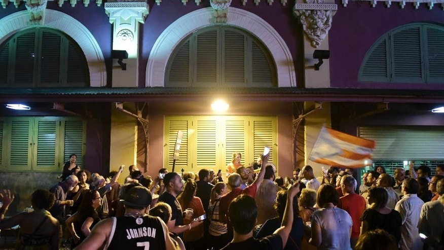 People celebrate after learning that President Barack Obama commuted the sentence for Puerto Rican nationalist Oscar Lopez Rivera, in San Juan, Puerto Rico, Tuesday, Jan. 17, 2017. Many Puerto Ricans have long demanded his release, and some wept with emotion upon hearing the news while others began preparing for all-night parties announced on social media. (AP Photo/Carlos Giusti)