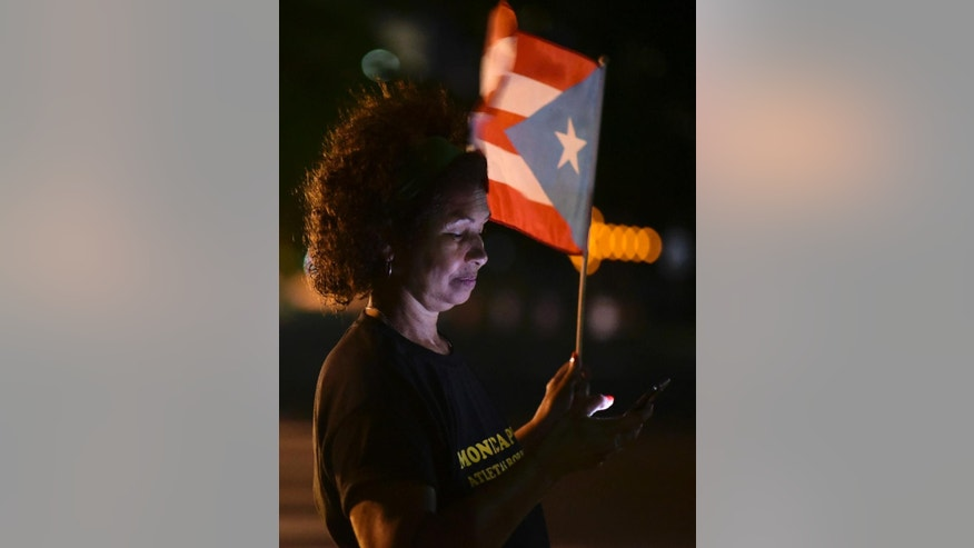 A woman waves a Puerto Rican flag outside the Federal Courthouse building after learning that President Barack Obama commuted the sentence for Puerto Rican nationalist Oscar Lopez Rivera, in San Juan, Puerto Rico, Tuesday, Jan. 17, 2017. Many Puerto Ricans have long demanded his release, and some wept with emotion upon hearing the news while others began preparing for all-night parties announced on social media. (AP Photo/Carlos Giusti)