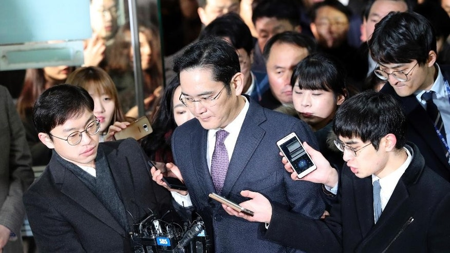 Lee Jae-yong, center, a vice chairman of Samsung Electronics Co. is questioned by reporters upon his arrival at the Seoul Central District Court in Seoul, South Korea, for a hearing Wednesday, Jan. 18, 2017.  The Seoul Central District Court will decide whether to arrest Lee after prosecutors requested the arrest earlier this week. (AP Photo/Lee Jin-man)