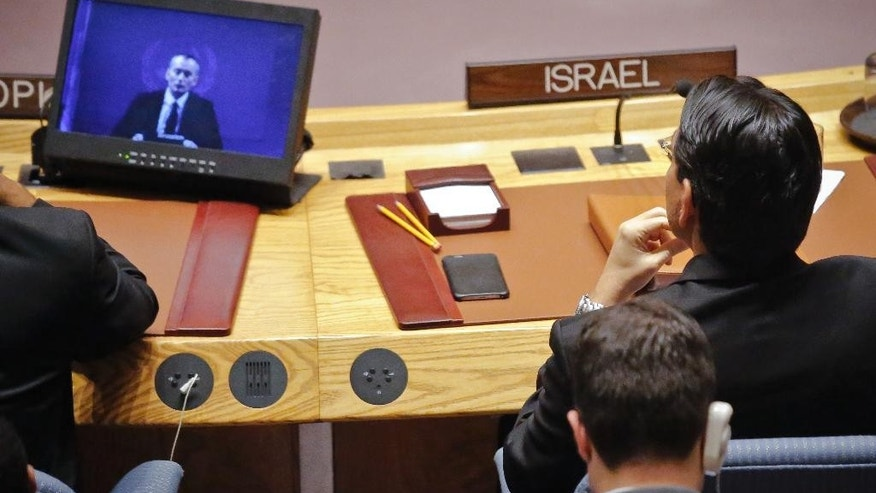 Israel U.N. Ambassador Danny Danon, right, watches a video broadcast of Nickolay Mladenov, United Nations Special Coordinator for the Middle East Peace Process, during a Security Council debate on the Middle East conflict Tuesday, Jan. 17, 2017 at U.N. headquarters. (AP Photo/Bebeto Matthews)