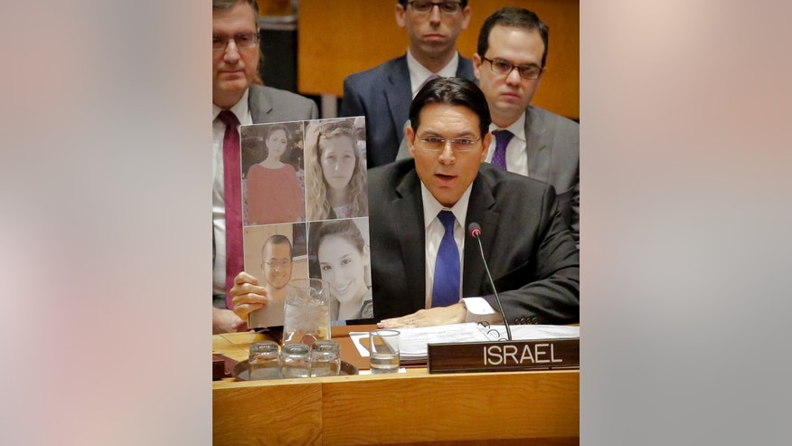 Israel U.N. Ambassador Danny Danon display pictures of four victims of a recent attack in Israel, as he speaks during a Security Council debate on the Middle East conflict Tuesday, Jan. 17, 2017, at U.N. headquarters. (AP Photo/Bebeto Matthews)