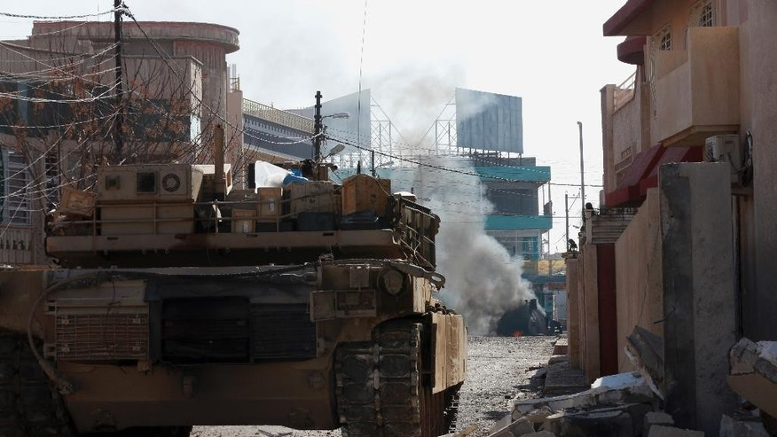 A tank of Iraq's special forces destroys a suicide car bomb belonging to Islamic State militants during the fight to regain control of Andalus neighborhood in the eastern side of Mosul, Iraq, Monday, Jan. 16, 2017. Iraqi troops have begun to push Islamic State militants out of the last remaining neighborhoods between government-held territory in the eastern Mosul and the Tigris river which divides the city. (AP Photo/ Khalid Mohammed)