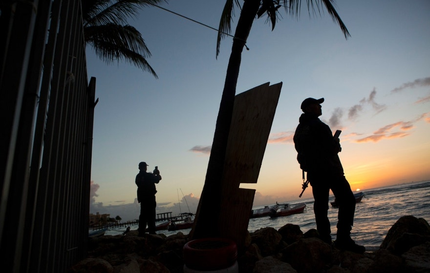 Municipal police watch the sunrise as they stand guard on the beach in front of the Blue Parrot club, a day after a deadly early morning shooting, in Playa del Carmen, Mexico, Tuesday, Jan. 17, 2017. Mexican authorities said Tuesday they are investigating whether extortion, street-level drug sales or a murder plot was the motive behind a shooting at an electronic music festival at a Caribbean resort town that left three foreigners and two Mexicans dead.(AP Photo/Rebecca Blackwell)