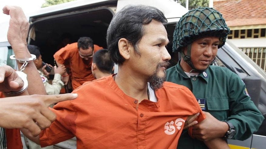 Meach Sovannara a convicted senior official of the opposition Cambodia National Rescue Party (CNRP) is escorted by prison guards during his arrival at Supreme Court in Phnom Penh, Cambodia, Wednesday, Jan. 18, 2017. Cambodia's Supreme Court on Wednesday held its hearing on convicted members of CNRP who were sentenced from 7 to 20 years in prison for leading a violent protest in 2014. (AP Photo/Heng Sinith)