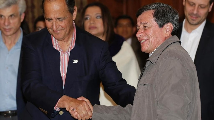 Colombian government representative Juan Camilo Restrepo, left, and rebel representative Pablo Beltran, of the National Liberation Army (ELN), shake hands at the end of a joint press conference in Quito, Ecuador, Wednesday, Jan. 18, 2017. Colombia's second-largest rebel group has agreed to free a prominent politician that it has held captive for almost a year, clearing the way for repeatedly postponed peace talks to begin next month. (AP Photo/Dolores Ochoa)