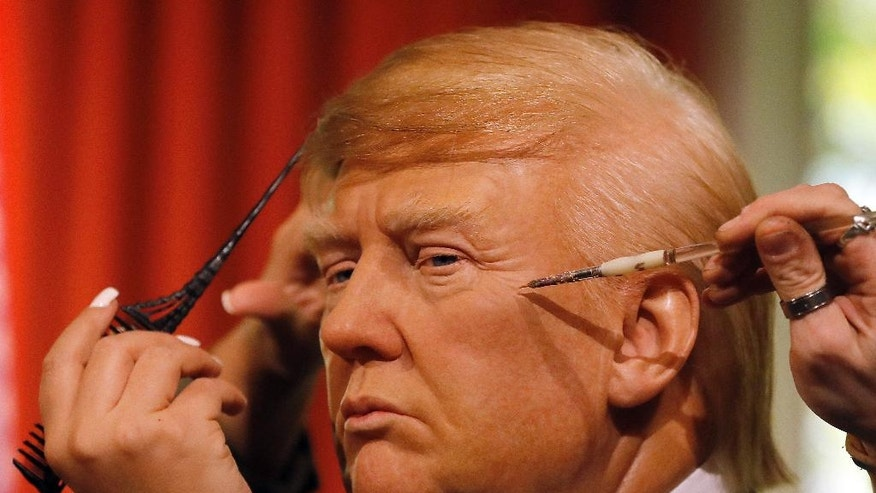 Madame Tussauds' designers apply the final touches to the wax figure of US President-elect Donald Trump, as they unveil the figure just days ahead of the American's Presidential Inauguration in Washington in London, Wednesday, Jan. 18, 2017. The figure will now reside in Madame Tussauds' London Oval Office alongside fellow famous politicians and global icons also immortalised in wax. (AP Photo/Frank Augstein)