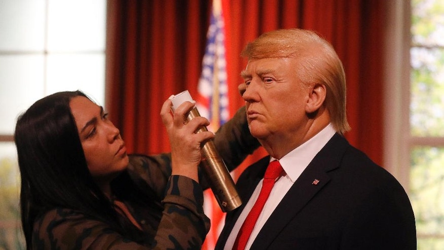 Madame Tussauds' designer Gema Sim adds hairspray to the wax figure of US President-elect Donald Trump, as they unveil the figure just days ahead of the American's Presidential Inauguration in Washington in London, Wednesday, Jan. 18, 2017. The figure will now reside in Madame Tussauds' London Oval Office alongside fellow famous politicians and global icons also immortalised in wax. (AP Photo/Frank Augstein)