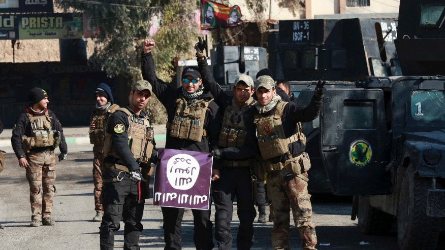 Iraq's special forces troops celebrate as they hold a flag of the Islamic State group they captured after regaining control of Andalus neighborhood in the eastern side of Mosul, Iraq, Monday, Jan. 16, 2017. Iraqi troops have begun to push Islamic State militants out of the last remaining neighborhoods between government-held territory in the eastern Mosul and the Tigris river which divides the city. (AP Photo/ Khalid Mohammed)