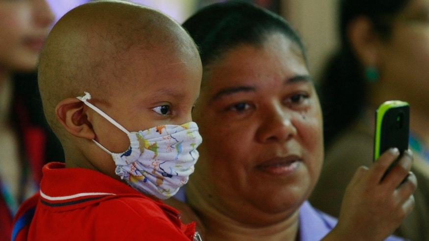 Antonio Ojeda, 3, looks at a cellular phone while receiving chemotherapy treatment at a pediatric hospital.