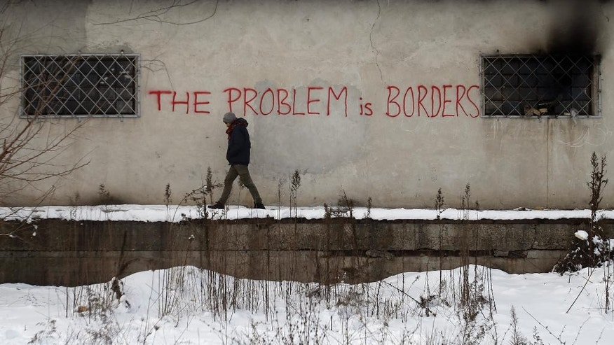 "In this Thursday, Jan. 12, 2017 photo, a migrant passes by a graffiti reading ""The problem is borders"" on a wall of a crumbling warehouse that has served as a make-shift shelter for hundreds of men trying to reach Western Europe in Belgrade, Serbia. It was a week in frigid hell for hundreds of migrants squatting in an abandoned warehouse in the Serbian capital of Belgrade while trying to move on toward Western Europe. (AP Photo/Darko Vojinovic)"