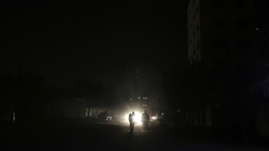In this Monday, Jan. 16, 2017 photo, Palestinians walk on a dark street during the power cut in Gaza City. At night, large swaths of the Gaza Strip plunge into darkness _ the result of chronic and worsening power outages. In crowded city streets, the only source of light comes from the headlights of passing cars. The power shortages are the worst to hit Gaza since Hamas seized control of the territory 10 years ago. (AP Photo/ Khalil Hamra)