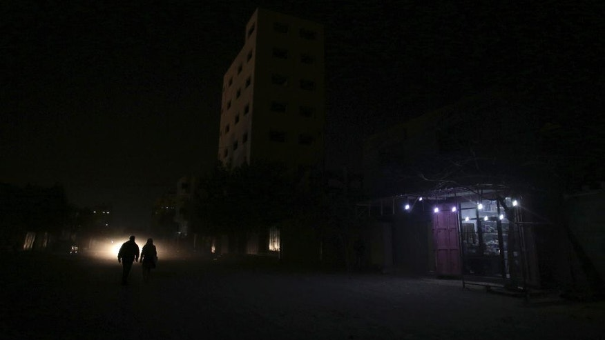 In this Monday, Jan. 16, 2017 photo, Palestinians walk on a dark street next to a grocery shop lit with a lamps powered by a battery during a power cut in Gaza City. At night, large swaths of the Gaza Strip plunge into darkness _ the result of chronic and worsening power outages. In crowded city streets, the only source of light comes from the headlights of passing cars. The power shortages are the worst to hit Gaza since Hamas seized control of the territory 10 years ago. (AP Photo/ Khalil Hamra)