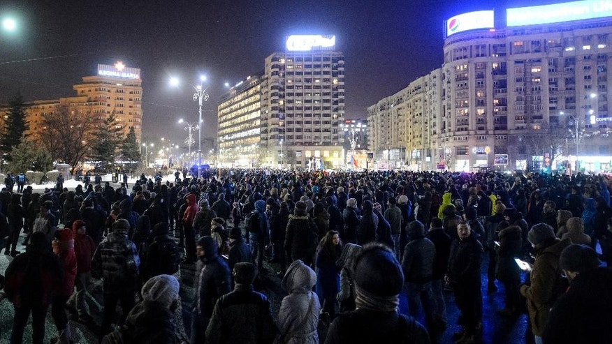 People stand in front of the government headquarters during protest against the government's plan to pardon thousands of prisoners through an emergency ordinance, in Bucharest, Romania, Wednesday, Jan. 18, 2017.  Several thousand people marched through the Romanian capital on Wednesday night to protest the government's plan to pardon thousands of prisoners, a surprise move to allegedly reduce overcrowding in prisons that would also benefit some notable government supporters. (AP Photo/Andreea Alexandru)