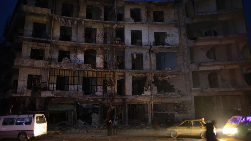 People walk next to a destroyed building in the once rebel-held Shaar neighborhood in the eastern Aleppo, Syria, Tuesday, Jan. 17, 2017. Parts of the once rebel-held eastern neighborhoods in the northern Syrian city of Aleppo are returning to normal nearly three weeks after opposition fighters left the city to the suburbs. (AP Photo/Hassan Ammar)