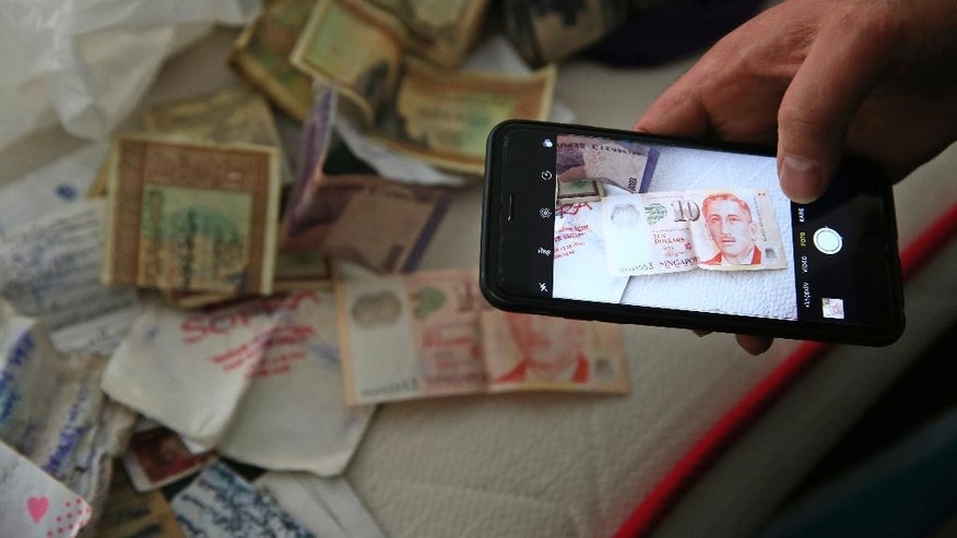 A member of the media uses his mobile phone to take pictures of belongings including banknotes of different currencies on a bed inside the flat where a suspect of New Year's Day nightclub attack was arrested during an overnight police raid, in Istanbul, Tuesday, Jan. 17, 2017. Turkish police said they captured the gunman who carried out the deadly New Year's nightclub attack in Istanbul, with officials saying Tuesday that he's an Uzbekistan national who trained in Afghanistan and confessed to the massacre.(AP Photo/Lefteris Pitarakis)